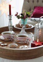 A Christmas tea break – tea cups and bowls of nuts next to a candle holder with a burning candle