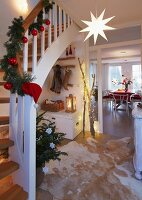 A hallway decorated for Christmas with a decorated banister and a view into the dining room