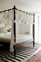 Antique four-poster bed with turned bedposts and white, draped fabric in Mediterranean interior