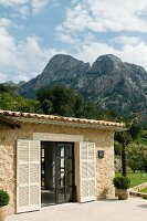 Mediterranean stone house with open terrace doors and pale shutters against mountain landscape