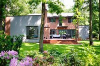 Modern house with brick facade, rendered elements, terrace & summer garden