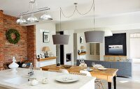 View across kitchen counter to dining area below pendant lamps with grey lampshades; lounge area in background with grey corner couch in open-plan interior with rustic atmosphere