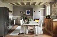 Chairs with loose white covers around simple dining table in eclectic kitchen with white, wood-beamed ceiling