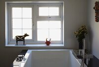 Detail of designer bathtub with angular taps, metal animal sculpture and ceramic pot on windowsill in background
