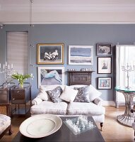 Large dish next to chess board on coffee table in front of pale, antique sofa in traditional living room with collection of pictures on wall painted blue-grey