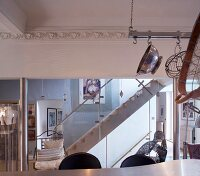 View across kitchen counter to staircase with glass balustrade