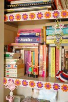 Detail of bookcase with bright, 70s floral trim on shelf edges