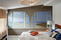 Trompe-l'œil beach mural on wall of bedroom with double bed