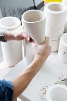 Hands shaping clay vase