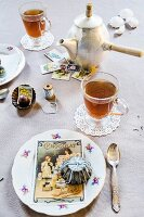 Vintage-style place setting on table with teacups, old cake tins and postcards
