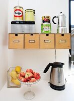Glass bowls of peaches and lemons next to kettle below wooden boxes in wall-mounted bracket with tin can and coffee maker on top