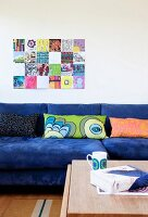 Sofa with blue cover and row of patterned scatter cushions below modern artwork on wall