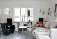 Black leather armchair, nest of coffee tables and modern sofa in rustic interior