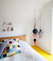 Colourful patchwork pillow on bed, various knitted balls hung from sloping ceiling and yellow-painted wooden floor