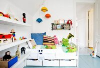 White bed with drawers and shelves of toys in child's bedroom
