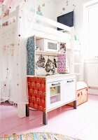 Child's bedroom with tulle curtains on white loft bed, pale wooden floor and patterned wallpaper