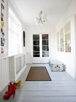 A loggia with grey floorboards, red and yellow shoes and a vintage suitcase and a glass cabinet in the background