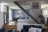 Elegant, open-plan living area with steel staircase and oak flooring in harmonious blend of grey and blue shades