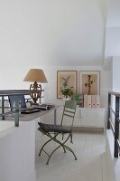 Study on white gallery level with pastel green vintage garden chair, antique table lamp and metal sideboard