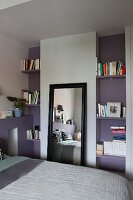 Mirror with black frame leant against wall between bookshelves in lilac niches in bedroom