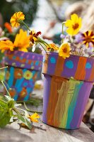 Yellow cut flowers in terracotta plant pots brightly painted by children