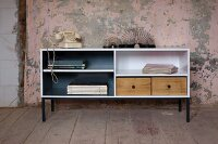 Upcycling - open-fronted sideboard painted white with wooden drawers against wall with peeling paint