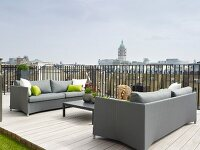 Elegant grey sofas and low coffee table on roof terrace with wooden decking