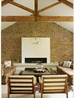 Armchairs with white cushions on wooden frames and sofas around low coffee table in front of fireplace in white chimney breast on brick wall