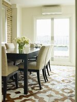 Dining table and chairs with pale, mottled upholstery on animal-skin patchwork rug with traditional pattern