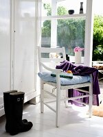White wardrobe, wooden armchair with seat cushion and black boots next to French windows