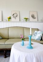 Cottage ambiance; round table, antique sofa in front of white-painted wainscoting with framed drawings on top