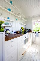 White kitchen counter in traditional country-house style below shelves of ornaments on white wooden wall