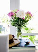 Peonies in glass vase, summer hat, gardening book and secateurs on white table in front of window