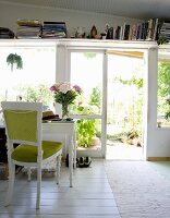 Full bookshelf and white vintage-style desk with upholstered chair in front of open French doors