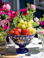 Fresh fruit in blue, vintage-style bowl on garden table