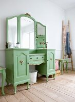 Green-painted, rustic dressing table with mirror and Vietnamese bamboo ladder on wooden floor