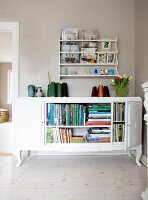 Old dresser used as bookcase below shelving unit on grey-painted wall