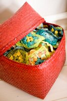 Red-painted rattan basket with open lid showing colourful crocheted squares with floral patterns
