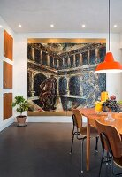 Large painting in dining area with extendible table, retro school chairs and orange pendant lamp