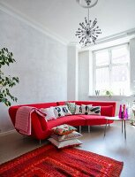 Bright red designer sofa with black and white scatter cushions in renovated town-house apartment with retro ambiance