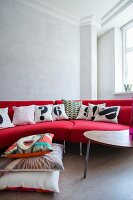 Bright red designer sofa with black and white scatter cushions and stacked cushions on floor in renovated period building with retro ambiance