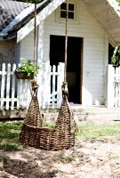 Wicker swing hanging outside white wooden house