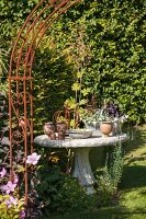 View through rusty trellis arch to garden ornaments on stone table in antique Greek style