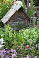 Wooden bug hotel in flowering garden