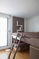 Ladder leading to loft bed lowered over sofa with drawers