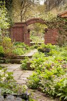 Landscaped beds in idyllic garden with arched gateway in brick wall