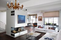 Open-plan interior with white sofas in front of open fireplace below blue modern artwork on free-standing chimney breast