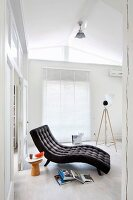 Charcoal grey, button-tufted lounger, stool used as side table and books on floor in white, purist interior