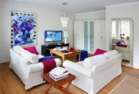 Living room furnished in white with bold accents of magenta and royal blue