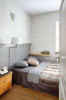 Bedroom with double bed, wood-clad dado and polka-dot wallpaper in shades of grey
